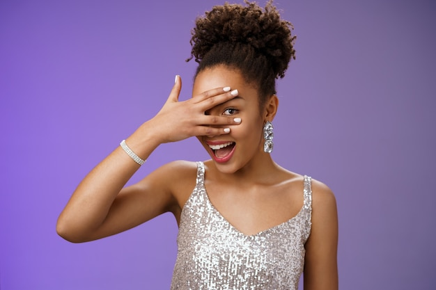 Close-up elegante donna afroamericana acconciatura afro accessori brillanti scintillanti vestito d'argento nascondendo il viso sbirciando attraverso le dita sguardo divertito sorpreso anticipando regalo interessante.