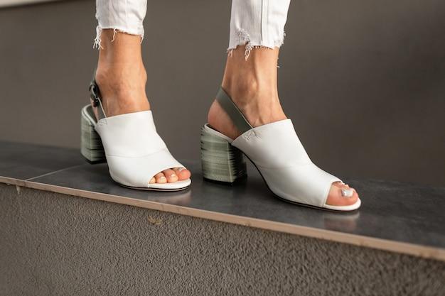 Primo piano delle gambe femminili alla moda in scarpe estive bianche in pelle alla moda su uno sfondo grigio.