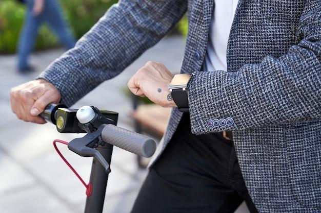 Primo piano di un elegante uomo d'affari di mezza età che controlla il tempo stando in piedi con uno scooter elettrico