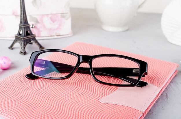 Close up occhiali da vista da donna alla moda nero sul taccuino rosa,