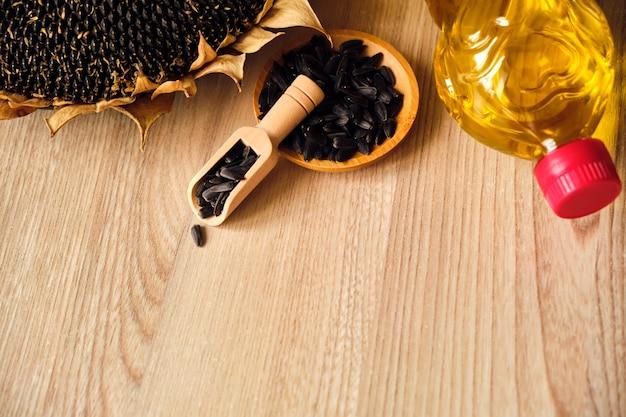 Primo piano di girasoli, bottiglia con olio e semi di girasole