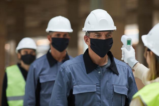 Primo piano del supervisore che misura la temperatura dei lavoratori con termometro senza contatto in cantiere, sicurezza contro il virus corona