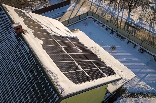 Chiudere la superficie del tetto di una casa ricoperta di pannelli solari in inverno con la neve sulla parte superiore.