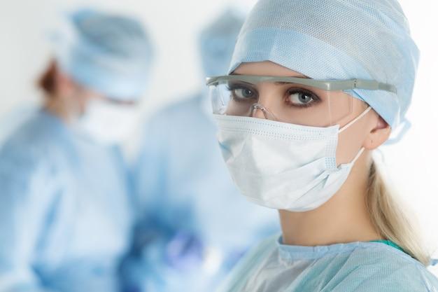 Primo piano della donna del chirurgo che osserva con i colleghi che effettuano nella sala operatoria