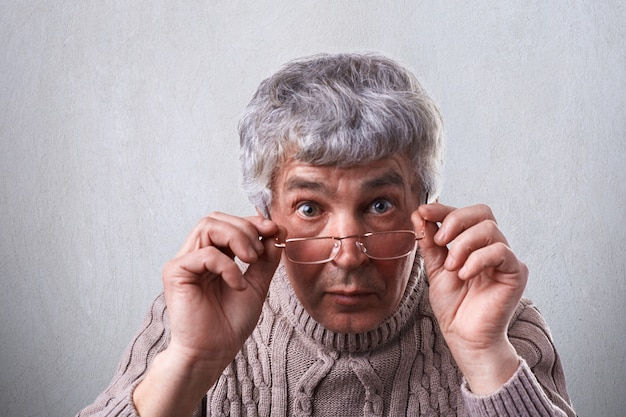 Primo piano dell'adulto sorpreso con i capelli grigi e le rughe con gli occhiali. uomo anziano toccando i suoi occhiali guardando con gli occhi spalancati nella fotocamera essere stupito di sentire alcune notizie