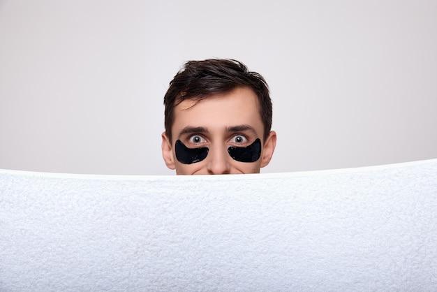 Uomo sorpreso primo piano in chiazze nere sotto i suoi occhi.