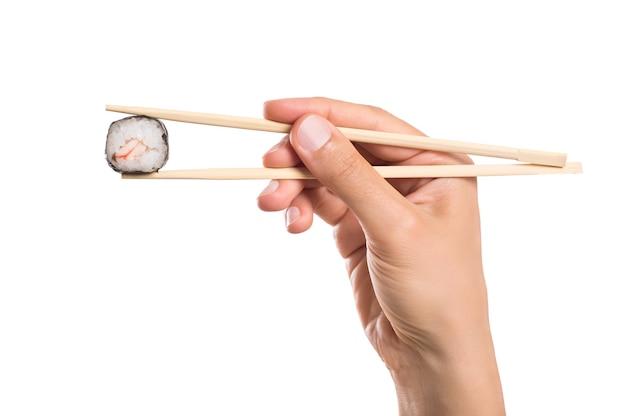 Primo piano di sushi roll tenuto con le bacchette isolato su bianco
