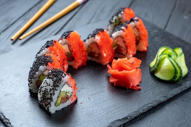 Chiuda sul rotolo di sushi con il caviale di tobico rosso e nero, il formaggio cremoso e il salmone. sushi sul piatto scuro di pietra su fondo di legno nero con lo spazio della copia. cibo giapponese. frutti di mare. dieta, salutare
