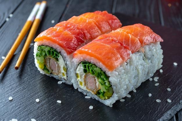 Chiuda sul rotolo di sushi con tonno, crema di formaggio e salmone. sushi sul piatto scuro di pietra su fondo di legno nero con lo spazio della copia. cibo giapponese. frutti di mare. dieta, salutare
