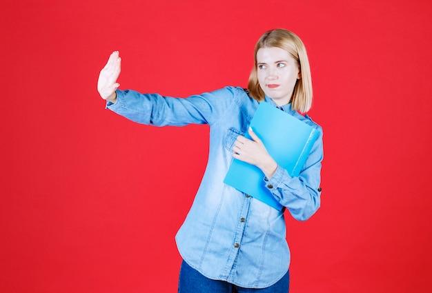 Chiuda sulla ragazza sospettosa dell'allievo dell'adolescente che tiene la cartella blu dei documenti e che mostra il gesto di arresto