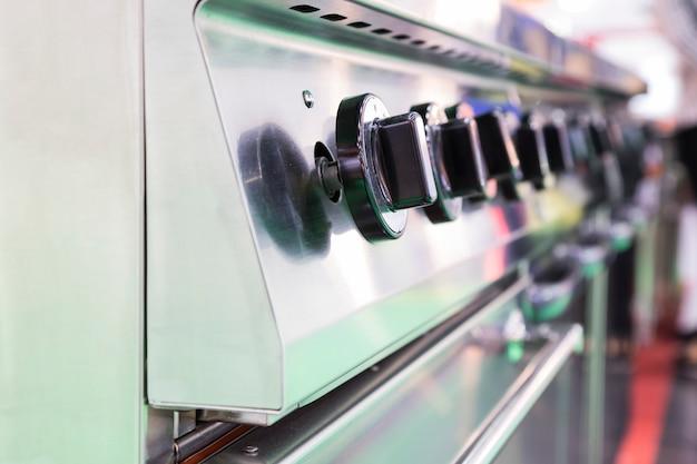 Chiuda sull'interruttore del fornello di gas bruciante della cucina