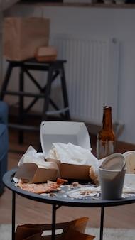 Primo piano del tavolo con gli avanzi su di esso in un soggiorno disordinato e disordinato vuoto