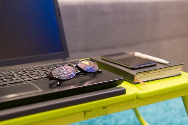 Primo piano di una workstation da tavolo con occhiali che si trovano sulla tastiera di un computer portatile aperto con accanto un diario e un telefono cellulare