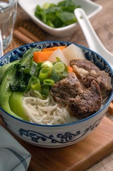 Chiuda in su del famoso cibo taiwanese con stinco di manzo brasato a fette e verdure in una ciotola sul tavolo di legno