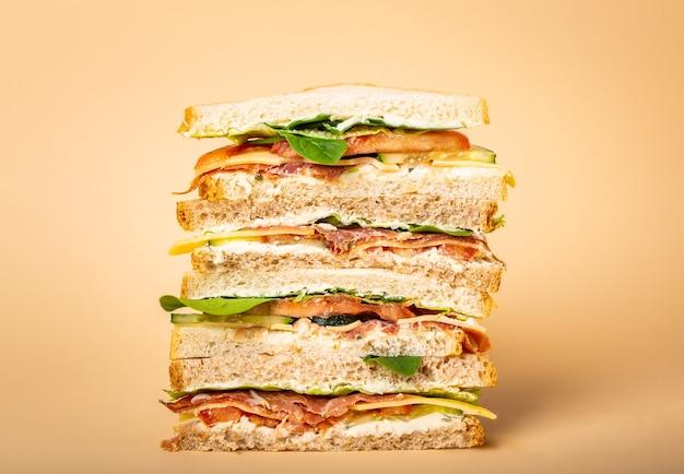 Close up di taglio alto gustoso panino con formaggio, prosciutto, prosciutto, lattuga fresca, pomodori, cetrioli su sfondo giallo pastello. sano panino gourmet per colazione o pranzo Foto Premium