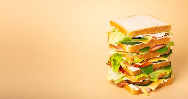 Close up alto intero gustoso panino con formaggio, prosciutto, prosciutto, lattuga fresca, pomodori, cetrioli su sfondo giallo pastello. panino gourmet sano per colazione o pranzo. spazio per il testo