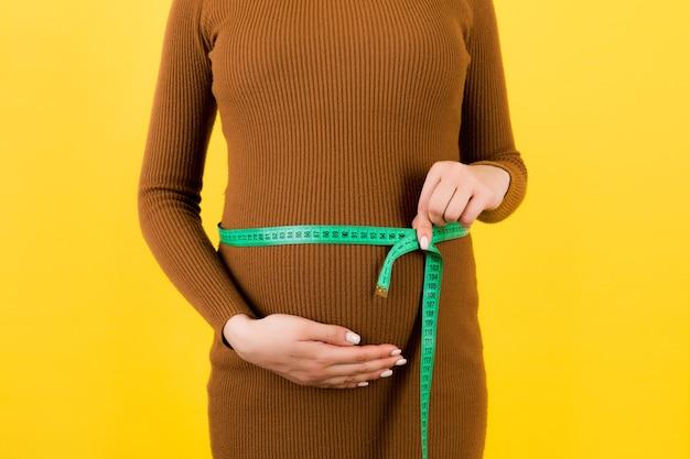 Primo piano del metro a nastro sulla pancia della donna incinta in abito marrone a sfondo giallo. misurazione dell'addome in crescita. copia spazio.