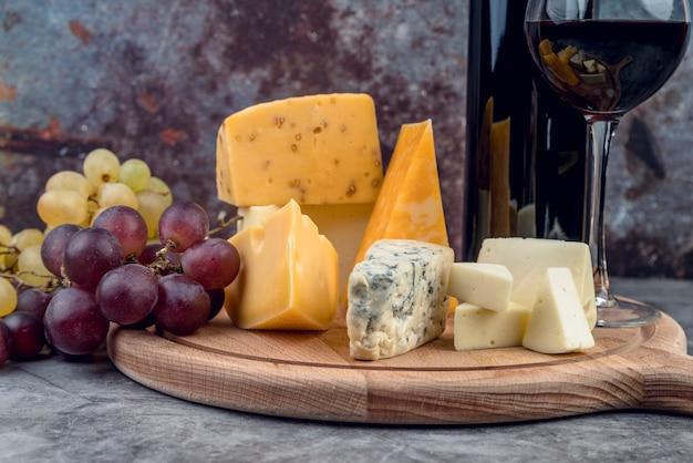 Selezione saporita del formaggio del primo piano con vino e l'uva