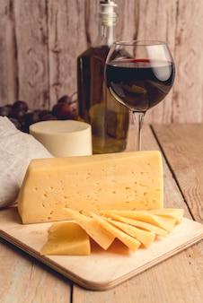 Formaggio saporito del primo piano con un bicchiere di vino