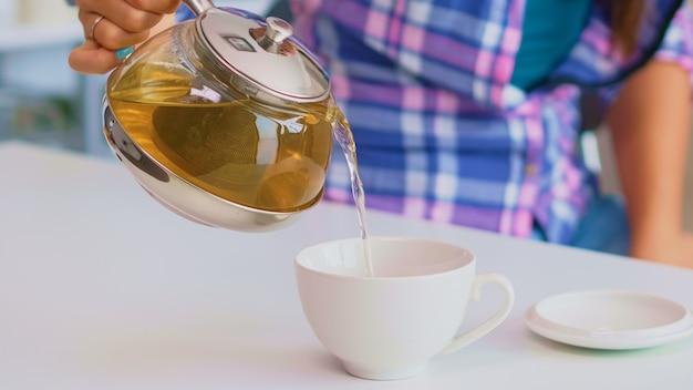 Primo piano di tè dal bollitore versare lentamente nella tazza di porcellana. giovane donna che prepara il tè verde in cucina al mattino a colazione, usando teiera, tazza da tè e foglie di erbe salutari.