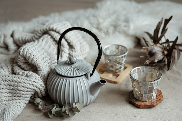 Primo piano della teiera in stile scandinavo con tè con elementi in maglia e dettagli decorativi.