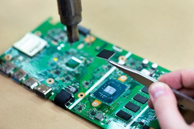 Primo piano di un tecnico che ripara un chip di computer con un saldatore, riscalda le parti e le scollega dalla scheda.
