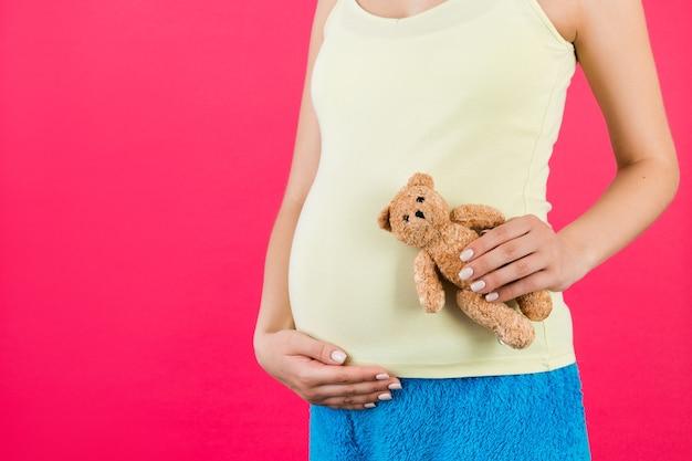 Chiuda in su dell'orsacchiotto in mano della donna incinta a sfondo rosa. la futura madre indossa abiti colorati per la casa. concetto di maternità. copia spazio.