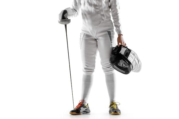 Chiuda in su della ragazza teenager in costume da scherma con la spada in mano isolata su fondo bianco. giovane modella caucasica femminile in movimento, azione