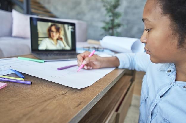 Primo piano di una studentessa adolescente che disegna con i pennarelli durante la lezione online con l'insegnante tramite chat video