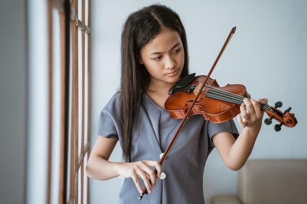 Primo piano di ragazza adolescente impara a suonare uno strumento violino