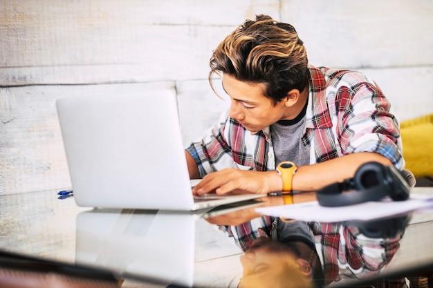 Primo piano di un adolescente con le cuffie che fissa il laptop mentre fa i compiti in silenzio - ragazzo con messa a fuoco interna
