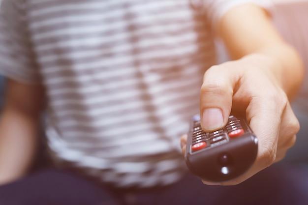 Chiudere il telecomando della televisione nelle mani dell'uomo casual che punta al televisore e accenderlo o spegnerlo. selezionare il canale guardando la tv sul divano di casa in soggiorno rilassarsi.