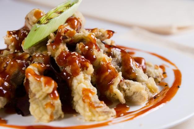 Primo piano di piatto per tempura con salsa e semi di sesamo
