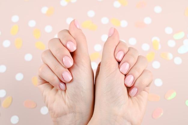 Chiuda in su delle mani tenere con manicure nuda su sfondo rosa pastello alla moda.