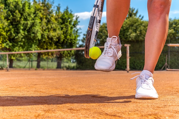 Primo piano sul giocatore di tennis sul campo, racchetta, palla e scarpe