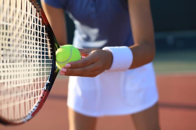 Primo piano di un giocatore di tennis che colpisce la palla con la racchetta.