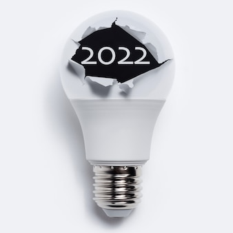 Primo piano del testo del 2022 all'interno del foro strappato sulla lampadina, su sfondo bianco.
