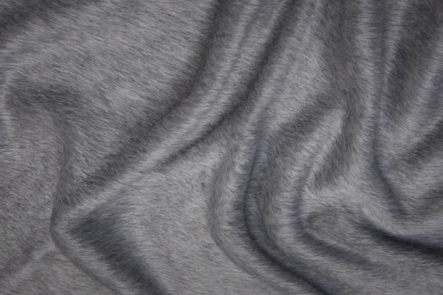 Chiudere la trama del tessuto per cappotto. tessuto di lana grigio. sfondo grigio.