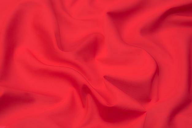 Trama ravvicinata di tessuto o stoffa rosso o rosa naturale dello stesso colore. trama del tessuto di cotone naturale, seta o lana o materiale tessile di lino. sfondo di tela rossa e rosa.
