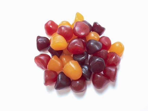 Texture ravvicinata di caramelle gommose multivitaminiche rosse, arancioni e viola. concetto di stile di vita sano.