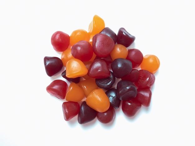 Texture ravvicinata di caramelle gommose multivitaminiche rosse, arancioni e viola su sfondo bianco. concetto di stile di vita sano.