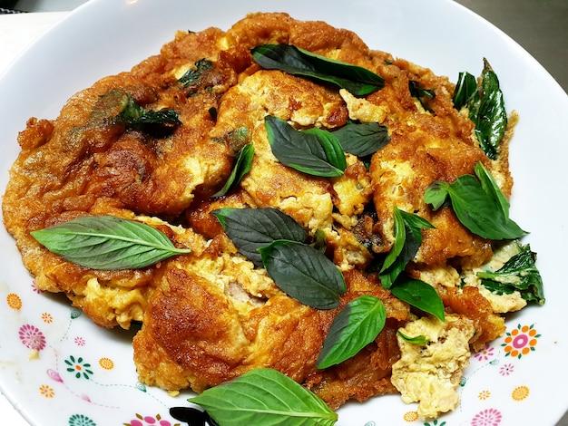 Close up omelette tailandese con foglia di basilico
