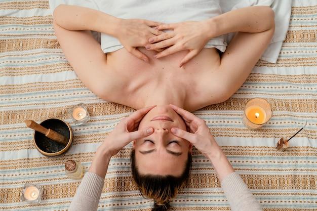 Primo piano terapista che massaggia le guance