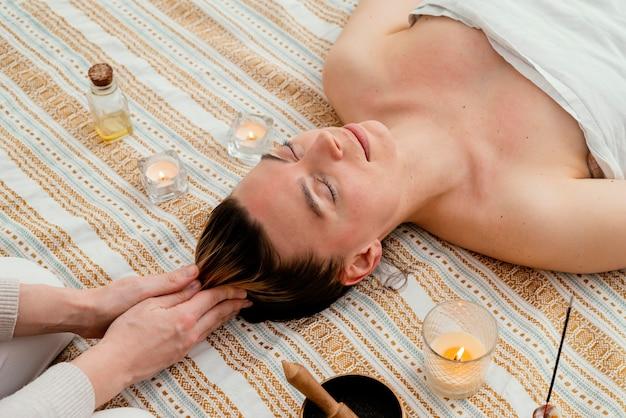 Primo piano terapista che massaggia il cuoio capelluto