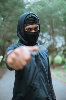 Primo piano del ladro in una maschera con un coltello che indossa una felpa con cappuccio nera ha puntato il coltello quando si è in piedi sulla strada