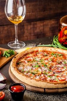 Primo piano sulla pizza sottile con pancetta e bicchiere di vino