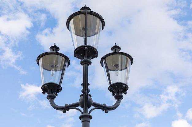 Close-up di tre lampioni neri su una colonna contro il cielo blu
