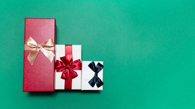 Close-up di tre scatole regalo sulla superficie verde con copia spazio