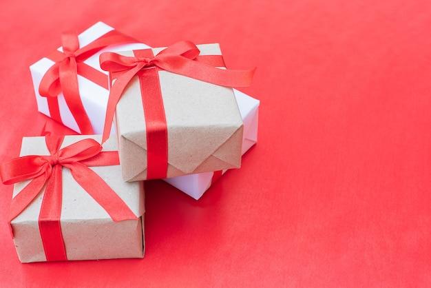 Close up tre scatole regalo. arco rosso del nastro con i contenitori di regalo su fondo rosso, scatola d'annata avvolta con lo spazio della copia