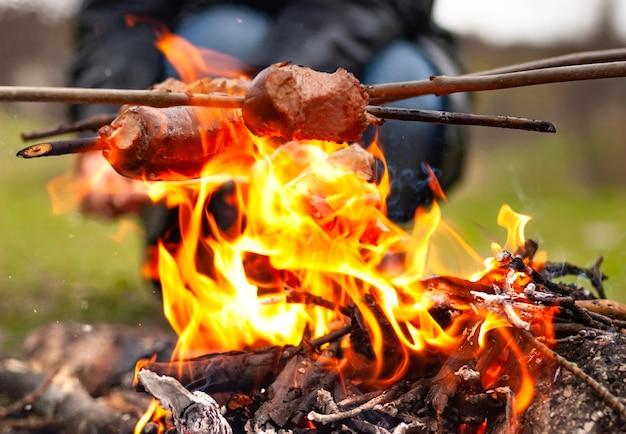 Primo piano tre salsicce su bastoncini sono fritte sul rogo sullo sfondo di una persona non identificata e di un paesaggio autunnale sfocato. concetto di campeggio di fine settimana e picnic in famiglia